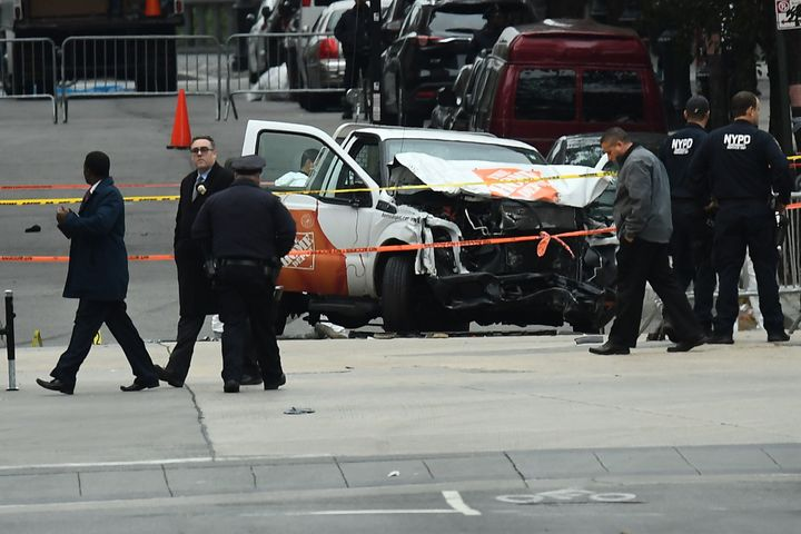 Investigators work around the wreckage of a Home Depot pickup truck a day after it was used in a terror attack in New York on