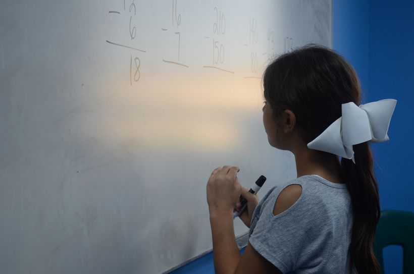 A young girl ponders her answer while studying math problems at Educare in Dearborn, Mich.
