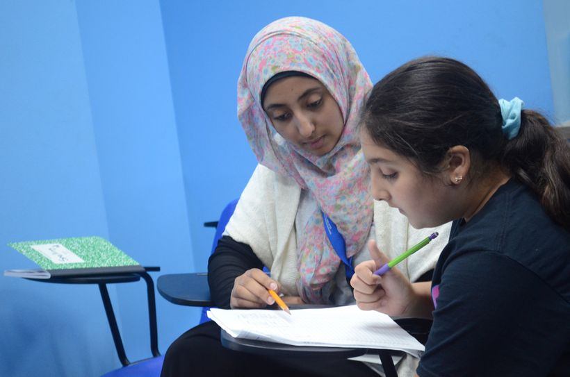 A teenage tutor with Educare helps a young student with her homework.