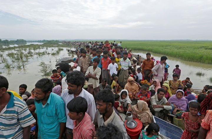 <i></i>Rohingya refugees wait to be taken to a refugee camp after crossing the Naf river at the Bangladesh-Myanmar border on