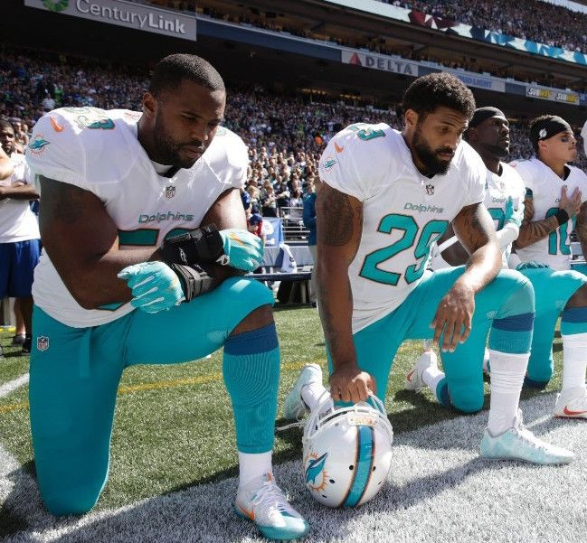 "Miami Dolphin players ""take a knee"" during the pre-game National Anthem to protest discrimination and police violence against"