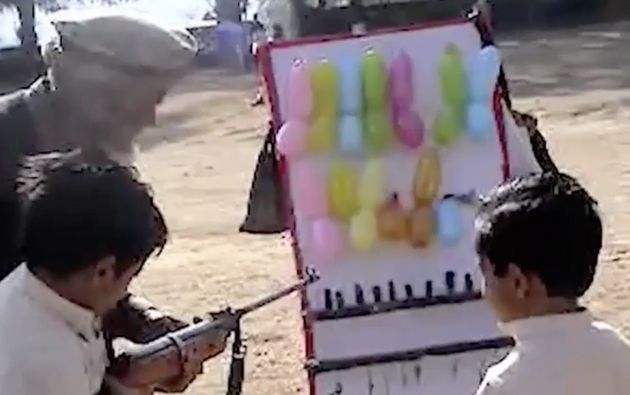A man instructs two boys on shooting balloons with a BB