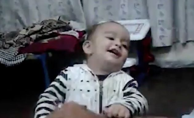 A gurgling little boy playfully bites an adult's