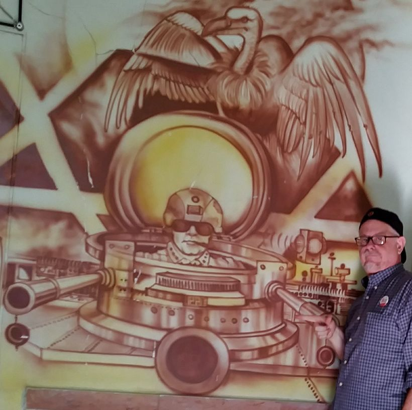 """Author beside vivid anti-US artwork inside the """"American Espionage Den,"""" the one-time besieged United States Embassy."""