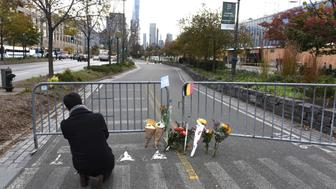 People stop at a memorial November 1, 2017 near the site of a terror attack in New York yesterday. The pickup truck driver who plowed down a New York cycle path, killing eight people, in the city's worst attack since September 11, was associated with the Islamic State group but 'radicalized domestically,' the state's governor said Wednesday. The driver, identified as Uzbek national named Sayfullo Saipov was shot by police in the stomach at the end of the rampage, but he was expected to survive. / AFP PHOTO / TIMOTHY A. CLARY        (Photo credit should read TIMOTHY A. CLARY/AFP/Getty Images)