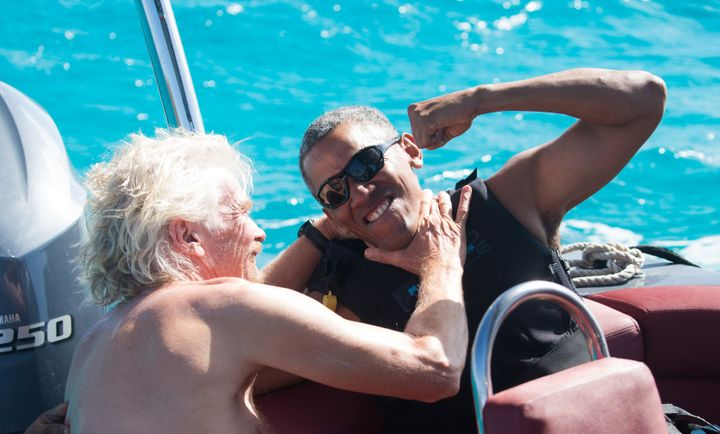 Former U.S. President Barack Obama and Richard Branson sit on a boat during Obama's holiday on Branson's Moskito island on Fe