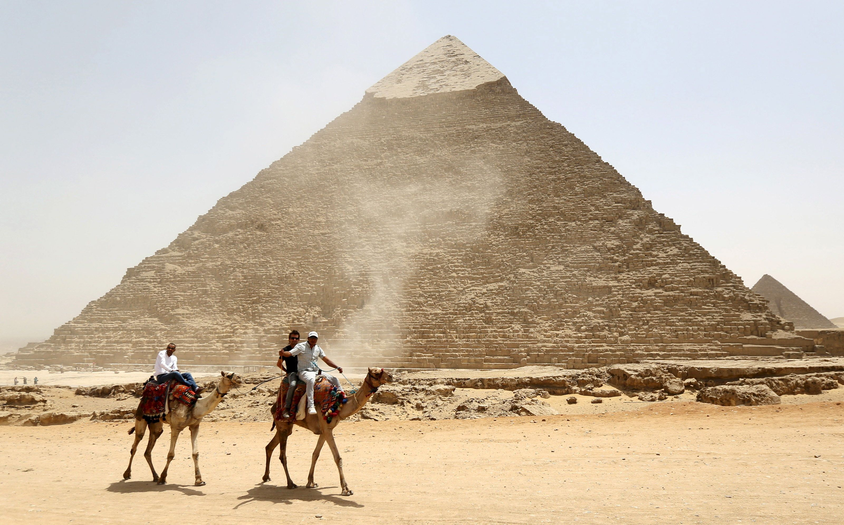 Tourists ride on camels next to the Pyramid of Khufu on the Great Pyramids of Giza, on the outskirts of Cairo, April 27, 2015. Local media reported Egypt's Minister of Antiquities Mamdouh al-Damaty attended the opening of two tombs that were under rennovation on Monday. One tomb belongs to the Priest of King Khufu while the other belongs to his eldest son. REUTERS/Mohamed Abd El Ghany