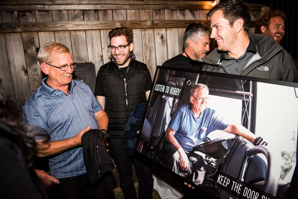 Bus driver Bobby Jansen is presented with a photo of himself on the bus during the wrap party.
