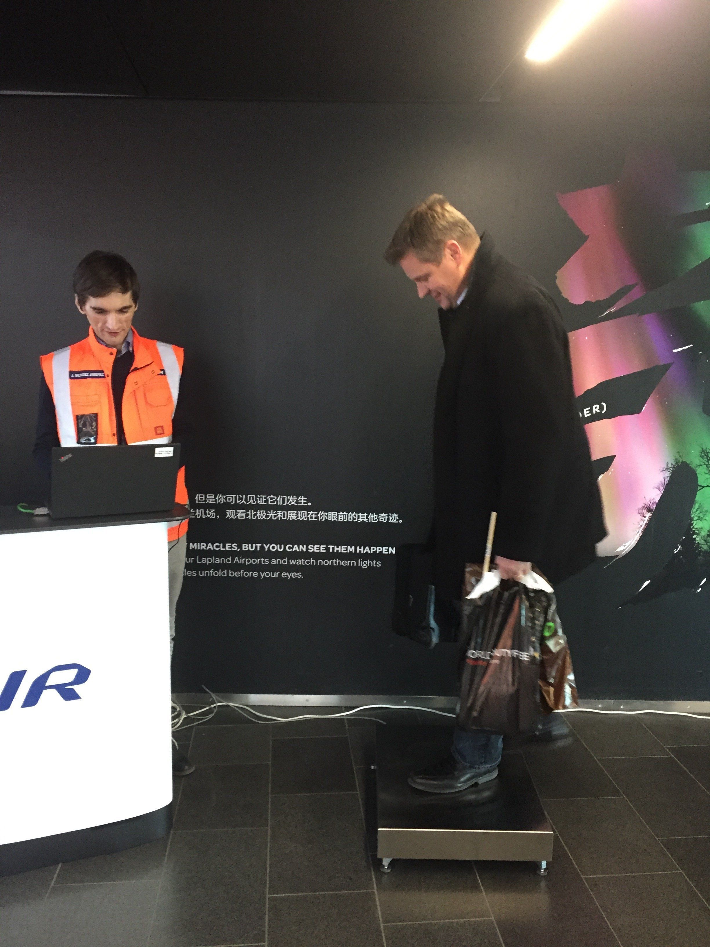 A Finnair pilot boards the scale with his carry-on bag at Helsinki Airport. He was one of some 180 volunteers to be weighed b