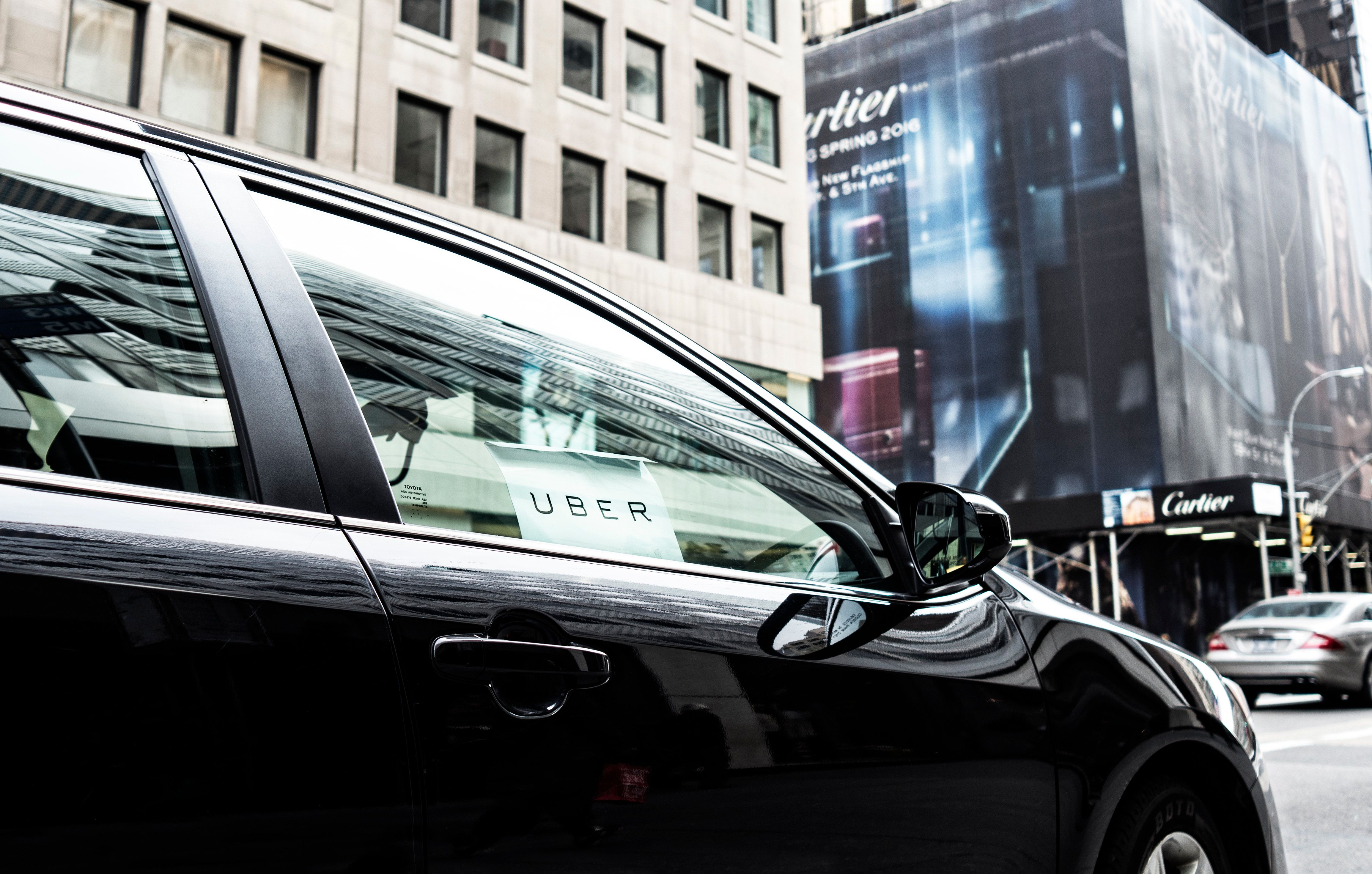 New York City, USA - March 5, 2016: Uber car service with sign in car window is waiting to pickup passengers on 5th Avenue in Manhattan, NY.