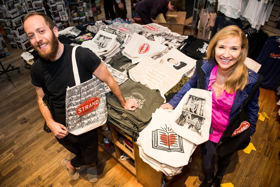 MacDonald and Strand co-owner Nancy Bass Wyden show off tote bags on sale at the Strand Bookstore in New York City.