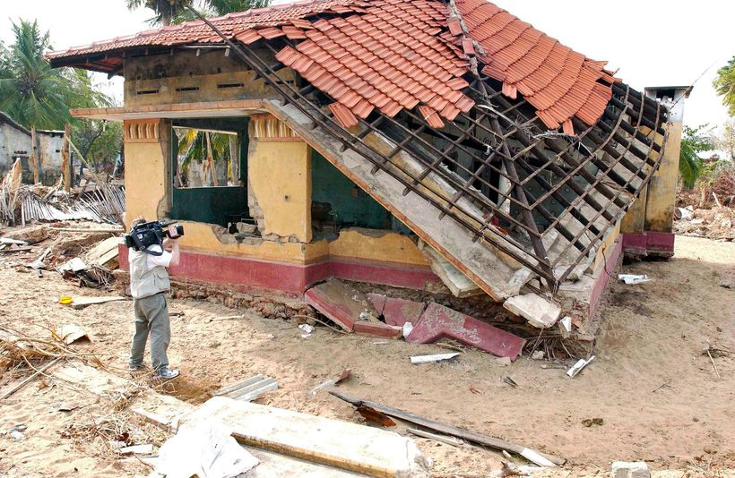A cameraman films some of the destruction caused by the tsunami of 26 December 2004 in Mullaitivu, a town in northeastern Sr