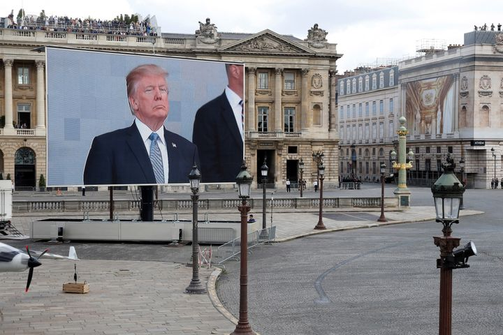 U.S. President Donald Trump appears on a giant screen on the Place de la Concorde during the traditional Bastille Day militar