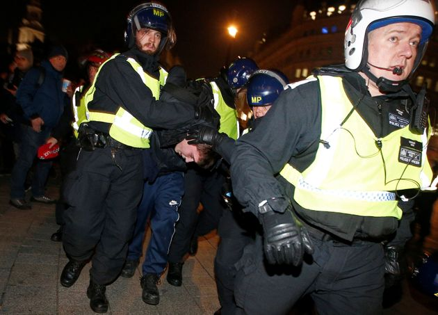 Police officers apprehend a protester during the march last