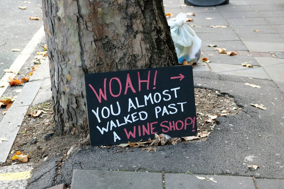 A sign advertising a wine shop lies on the same street asan estate agent which listed homes for...