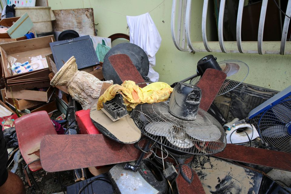 Juan Medina-Dishmey and his wife, Juana Ferrera, cleared out damaged belongings from their home in Valle...