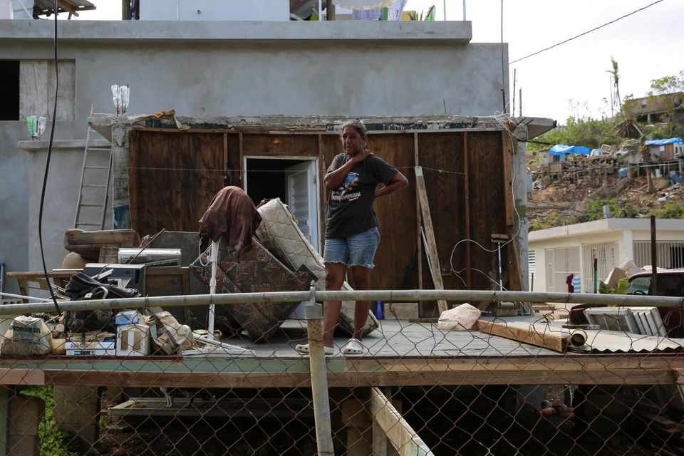A woman stands in the middle of what used to be her home in Canóvanas, Puerto Rico, on Oct. 14,