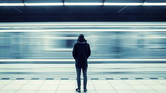 Lonely young man shot from behind at subway station with blurry moving train in background