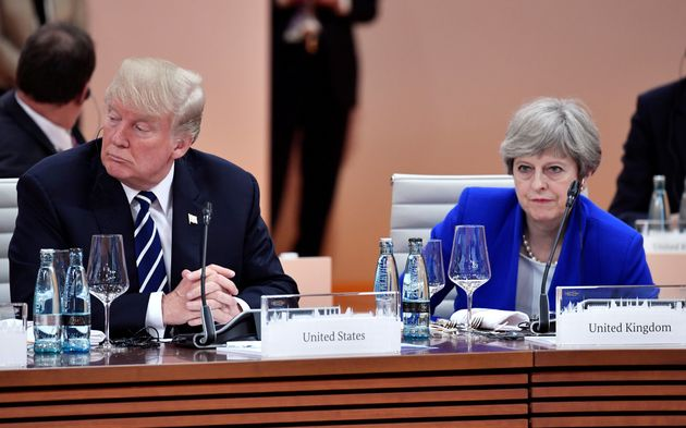 Trump and British Prime Minister Theresa May wait at the start of the first working session...