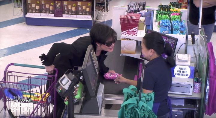 Kris Jenner leans in to whisper a secret to the cashier about a pack of razors.