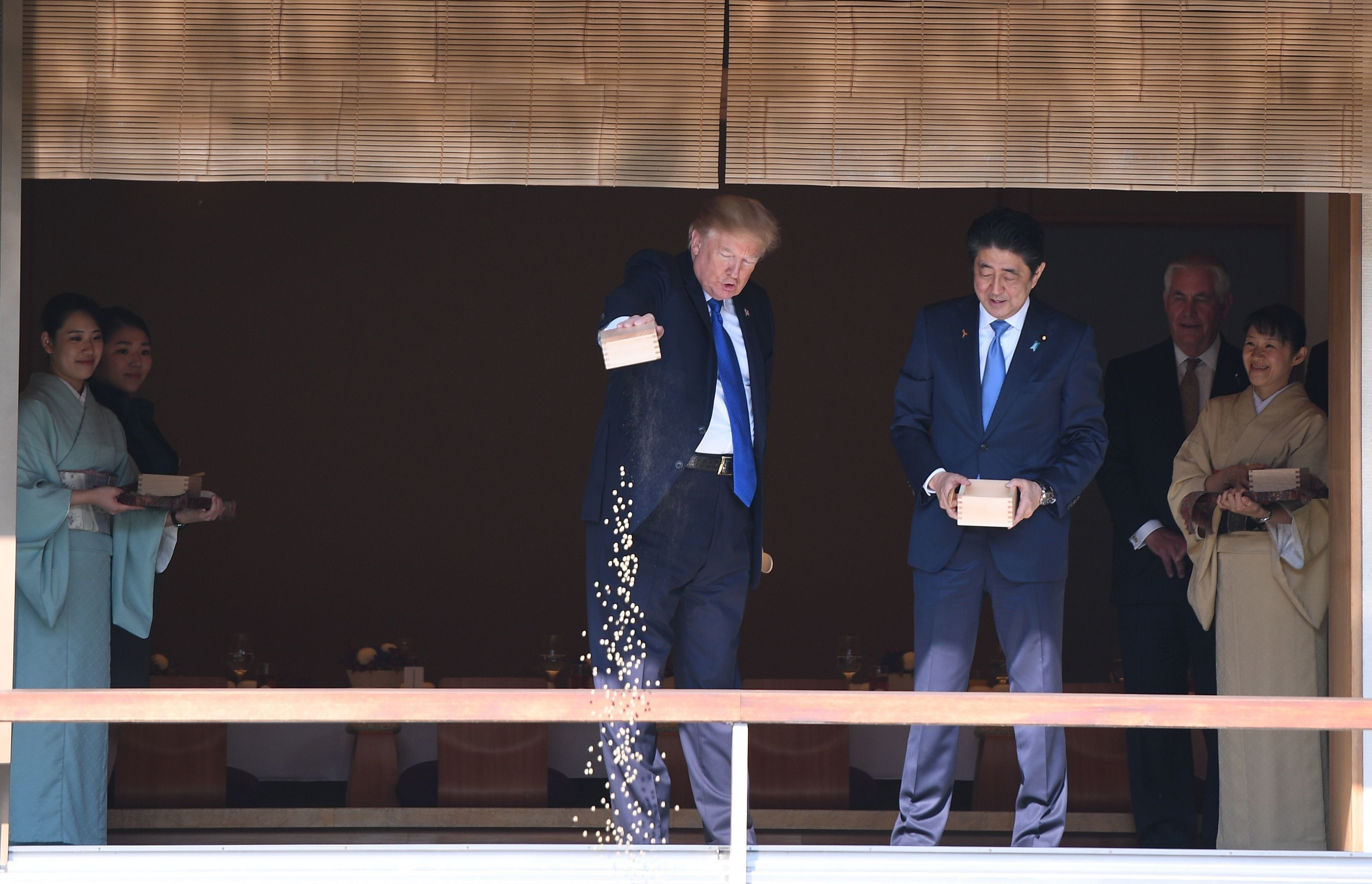 US President Donald Trump (C) feeds koi fish as Japanese Prime Minister Shinzo Abe (R)looks on during a welcoming ceremony in Tokyo on November 6, 2017. Trump lashed out at the US trade relationship with Japan, saying it was 'not fair and open', as he prepared for formal talks with his Japanese counterpart. / AFP PHOTO / JIM WATSON        (Photo credit should read JIM WATSON/AFP/Getty Images)