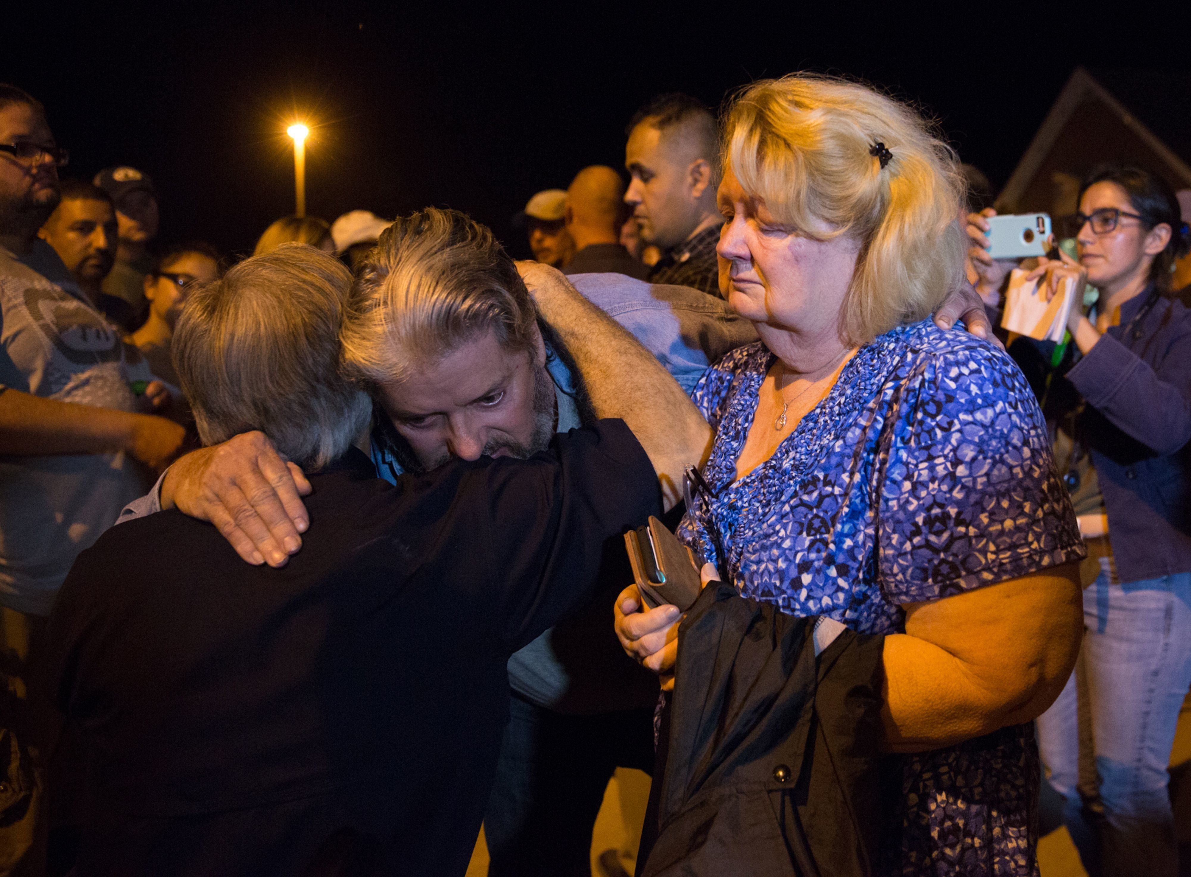 Ted and Ann Montgomery, employees at the First Baptist Church, are comforted by Texas Governor Greg Abbott (L) following a candlelight vigil held across the street from the church on November 5, 2017. 'There are 26 lives that have been lost. We don't know if that number will rise or not, all we know is that's too many, and this will be a long, suffering mourning for those in pain,' Abbott said during a press conference.  / AFP PHOTO / SUZANNE CORDEIRO        (Photo credit should read SUZANNE CORDEIRO/AFP/Getty Images)