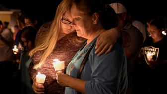 Local residents embrace during a candlelight vigil for victims of a mass shooting in a church in Sutherland Springs, Texas, U.S., November 5, 2017.  REUTERS/Mohammad Khursheed