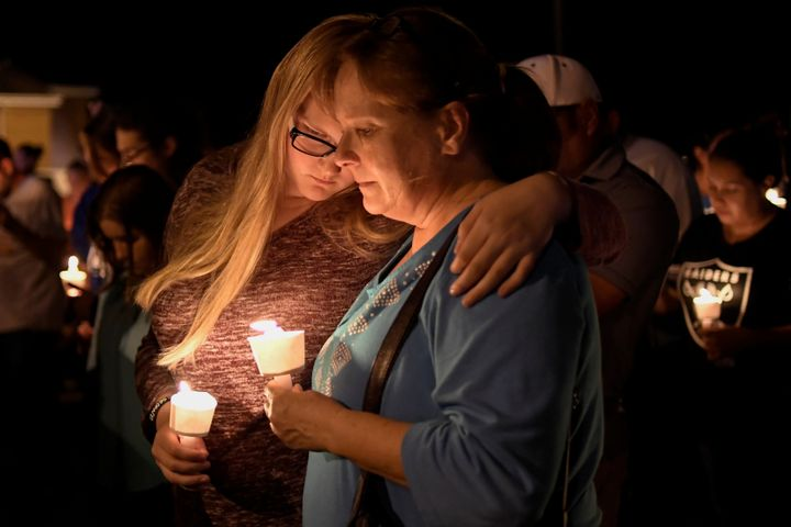 People embrace during a candlelight vigil for victims of a mass shooting at a church in Sutherland Springs, Texas.