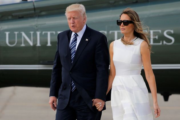 U.S. President Donald Trump and first lady Melania Trump hold hands as they arrive to board Air Force...