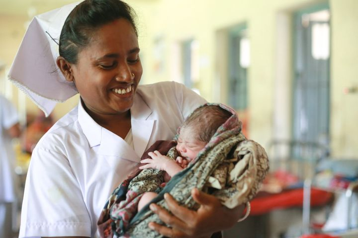 A midwife in&nbsp;<strong></strong>Bangladesh holds a 1-day-old baby.&nbsp;