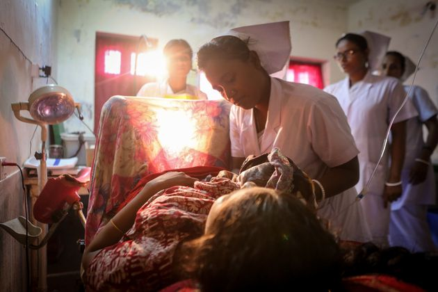 A midwife delivers a baby in