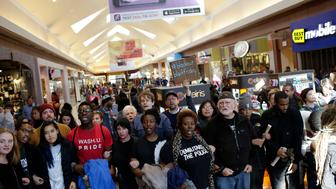 ST. LOUIS, MO - NOVEMBER 28 : Demonstrators protesting the shooting death of Michael Brown hold signs as they walk through Saint Louis Galleria mall yelling chants during Black Friday November 28, 2014 in St. Louis, Missouri. The mall was later closed. Some local businesses still remain closed to consumers in Ferguson, Missouri as tension continue to still run high in the community after Michael Brown, a 18-year-old black male teenager was fatally wounded by Darren Wilson, a white Ferguson Police officer on August 9, 2014. A St. Louis County 12-member grand jury who reviewed evidence related to the shooting decided Monday not to indict Wilson with charges sparking riots through out Ferguson. (Photo by Joshua Lott/Getty Images)