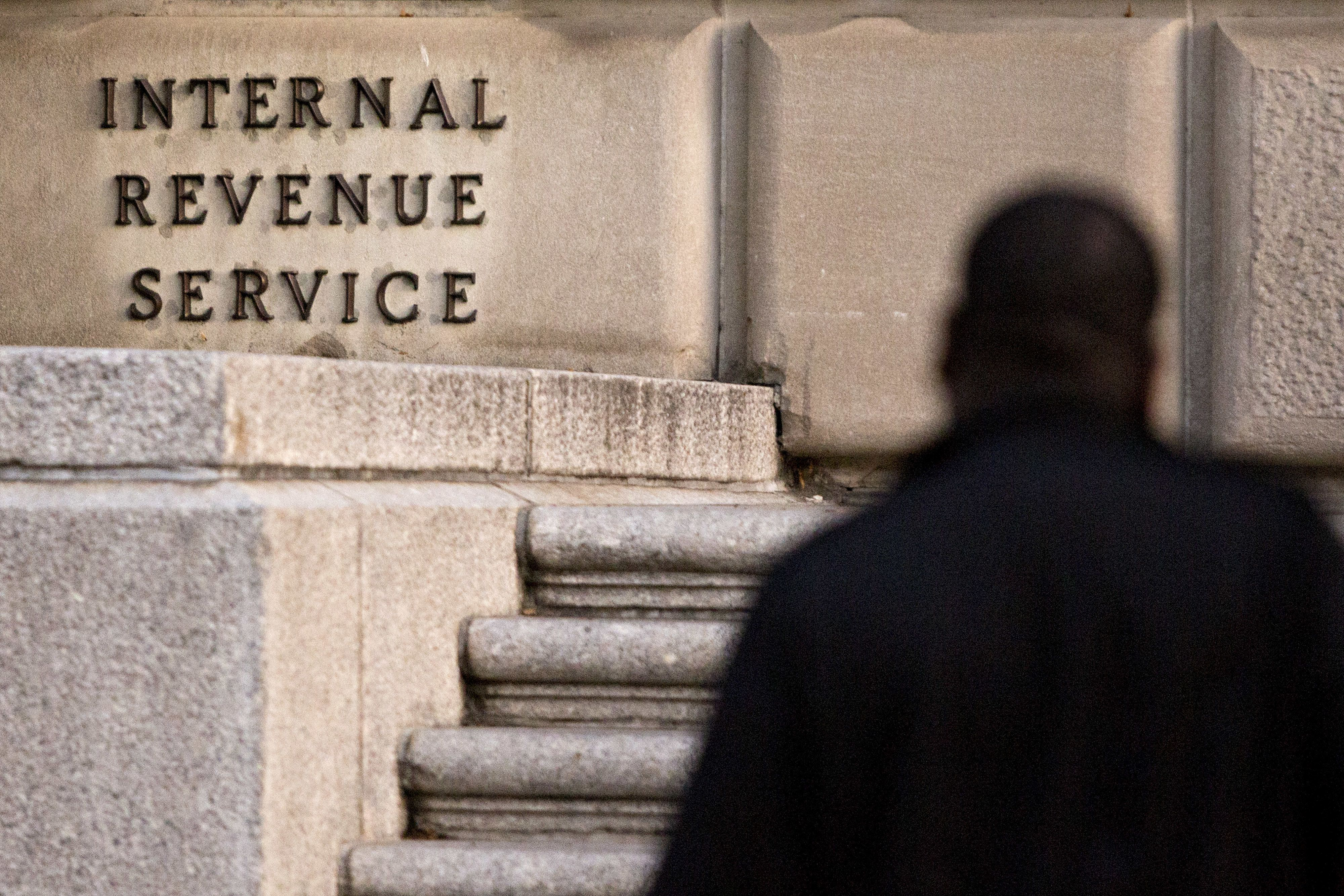 A man walks past the Internal Revenue Service (IRS) headquarters in Washington, D.C., U.S., on Friday, Oct. 20, 2017. President Donald Trump's top legislative priority took a major step forward as the Senate narrowly approved a budget vehicle for tax cuts -- but sharp divides over an array of non-binding amendments revealed the towering challenge he faces from here. Photographer: Andrew Harrer/Bloomberg via Getty Images