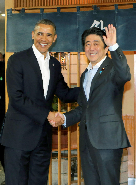 Obama and Abe shake hands in front of Sukiyabashi Jiro sushi restaurant.
