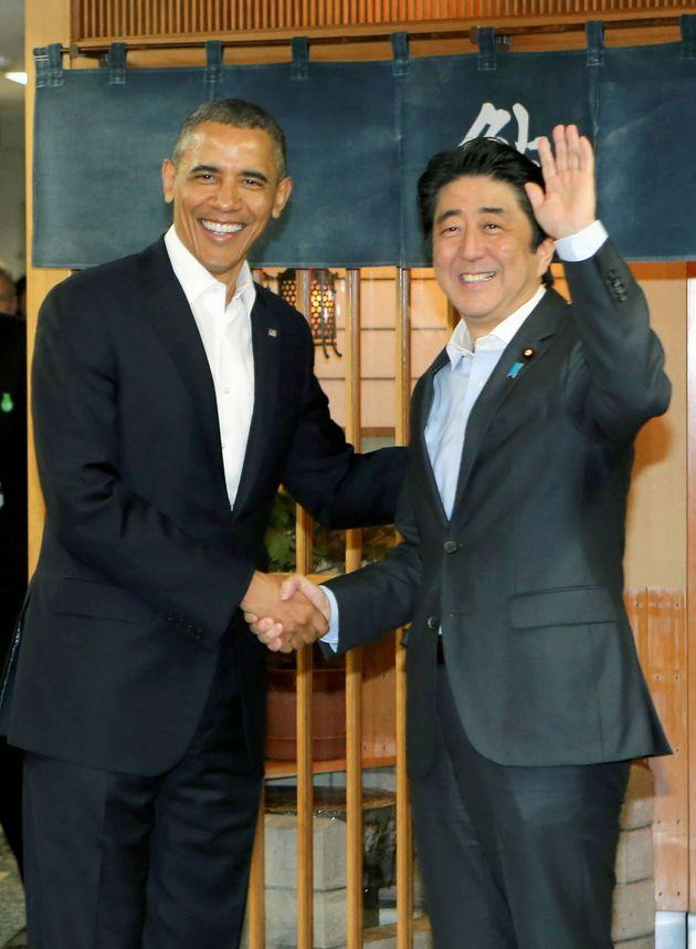 Obama and Abe shake hands in front of Sukiyabashi Jiro sushi