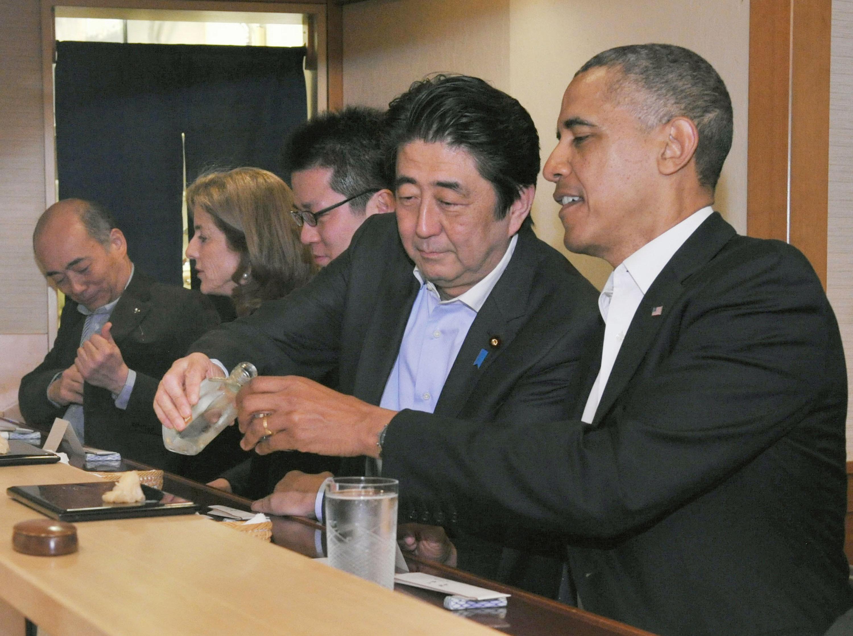 Japanese Prime Minister Shizo Abe fills U.S. President Barak Obama's glass during dinner at Sukiyabashi Jiro sushi restaurant