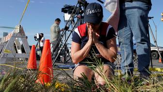 Rebecca Thompson prays after placing flowers near the site of the shooting at the First Baptist Church of Sutherland, Texas, U.S., November 6, 2017.  REUTERS/Rick Wilking