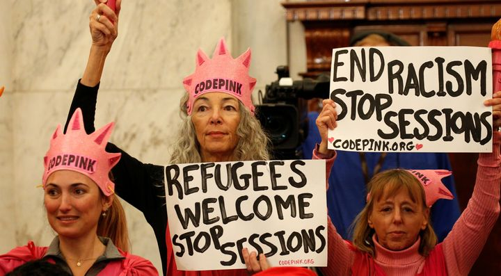 Protesters hold signs at the Senate Judiciary Committee confirmation hearing for Jeff Sessions to become U.S. attorney genera