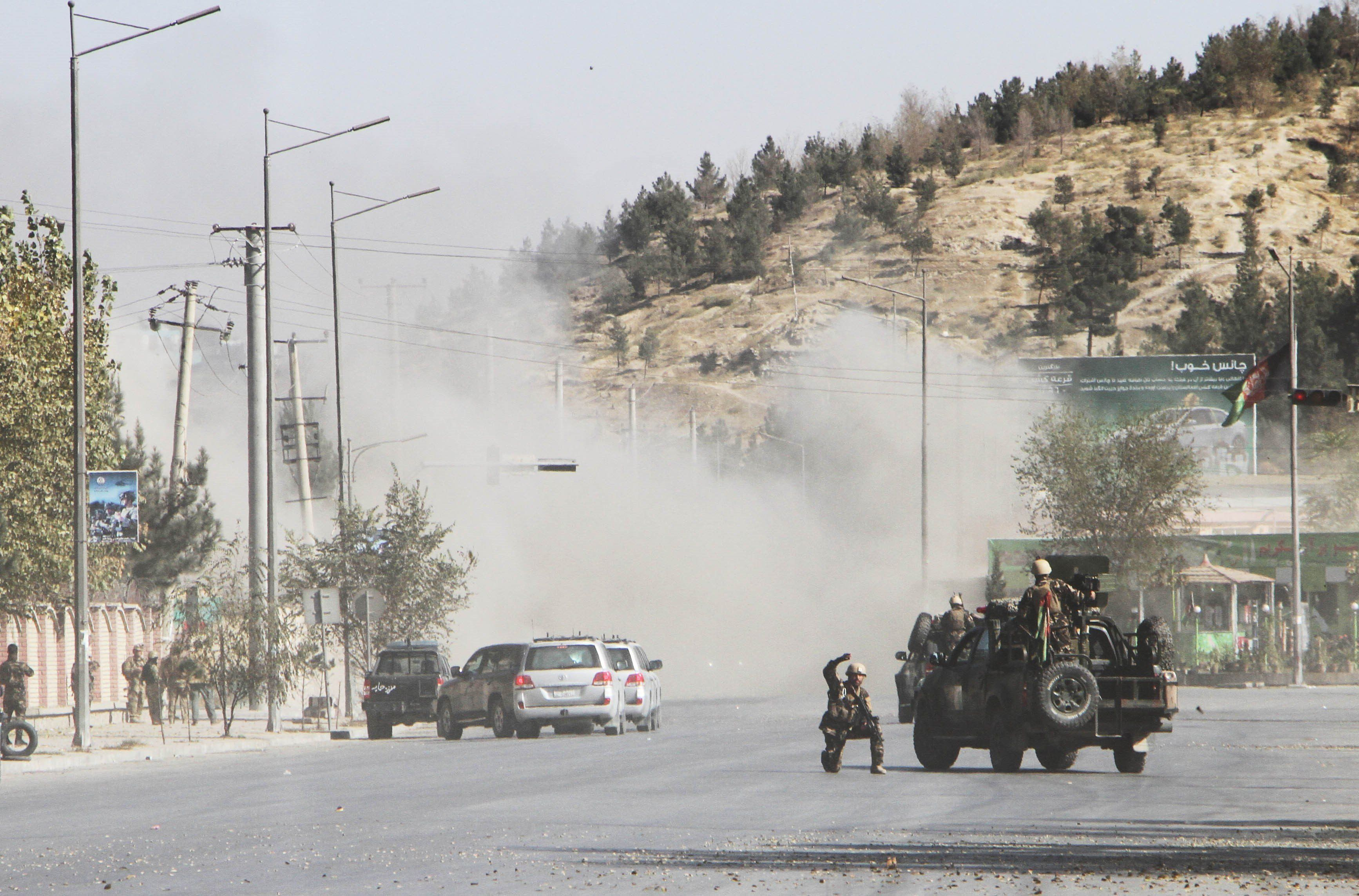 Afghan security officials take positions near the scene of an attack by armed men on the Shamshad TV station in Kabul, Afghan