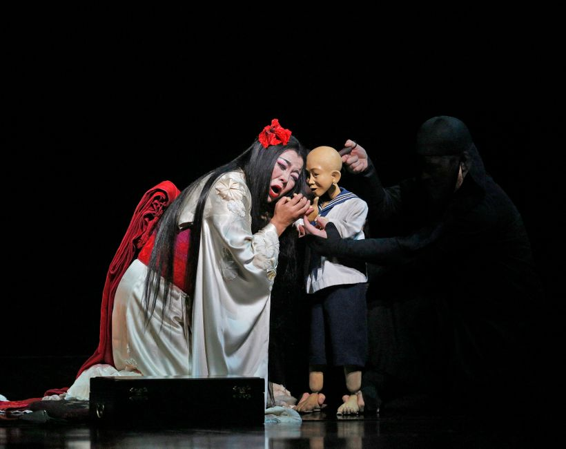 Hui He as Cio-Cio-San with the Bunraku puppet of her son in the Met Opera's <em>Madama Butterfly</em>.