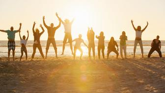 Twelve young people jumping at the beach of St.Peter-Ording in Germany in the fantastic sunset.