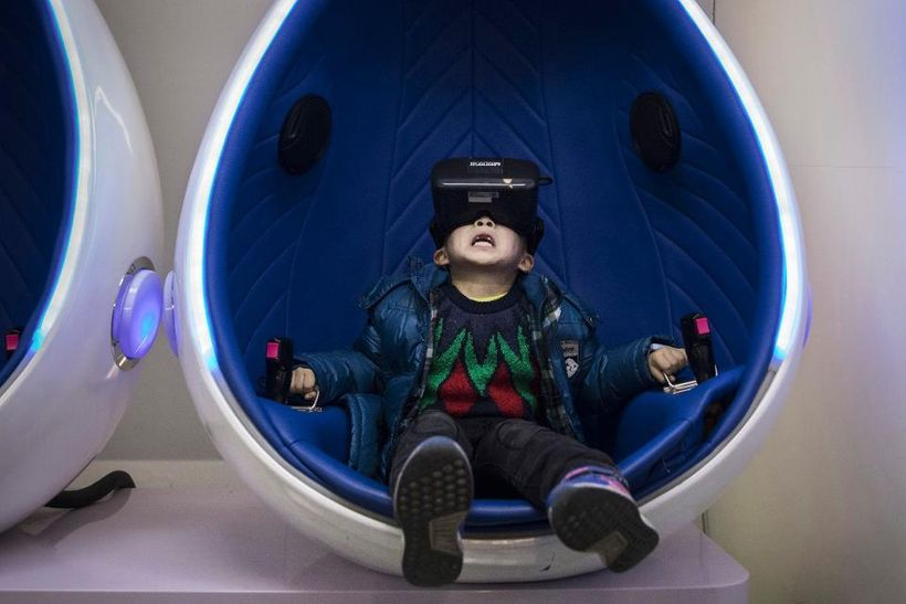 <em>BEIJING, CHINA - NOVEMBER 26: A Chinese boy reacts while wearing virtual reality (VR) glasses in a roller coaster simulat