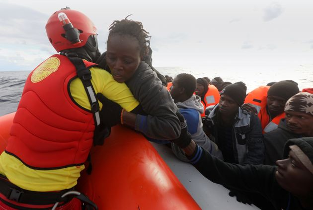 A lifeguard pulls a migrant woman to a rescue craft from an overcrowded raft in the central Mediterranean...