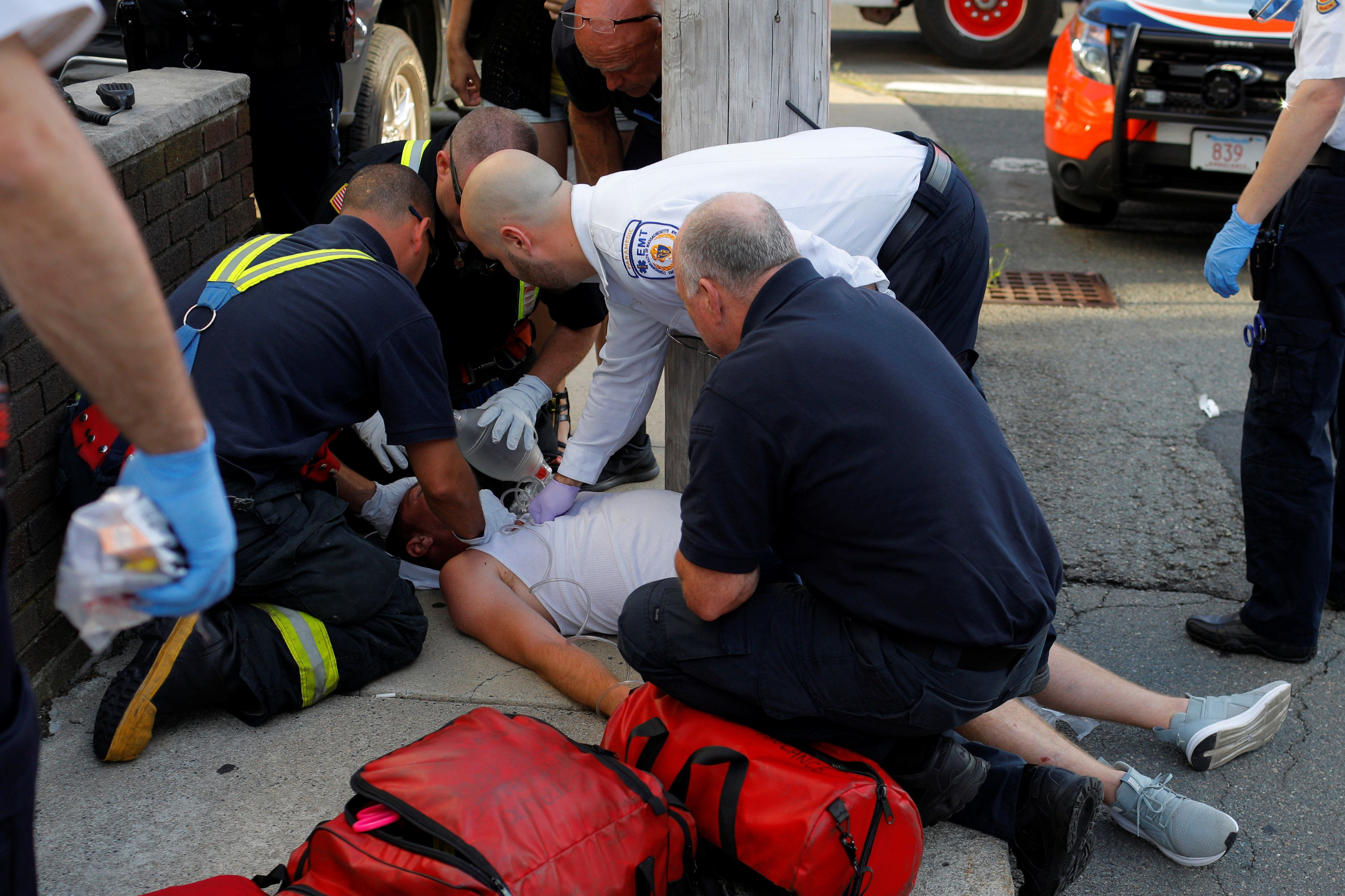 Paramedics and firefighters treat a 32-year-old man who was found unresponsive on a sidewalk after overdosing on opioids in E