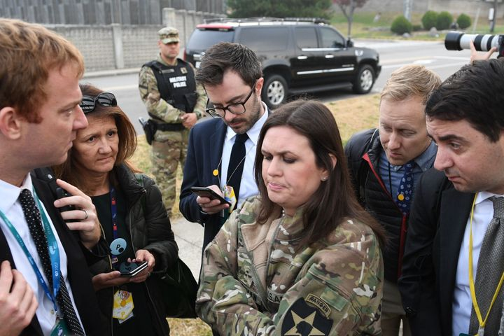 White House press secretary Sarah Huckabee Sanders (center) speaks to reporters after the helicopters returned from the