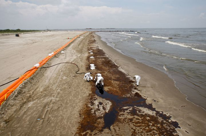 BP oil company contract workers remove oil that washed onto the beach at Grand Isle State Park in Louisiana on June 6, 2