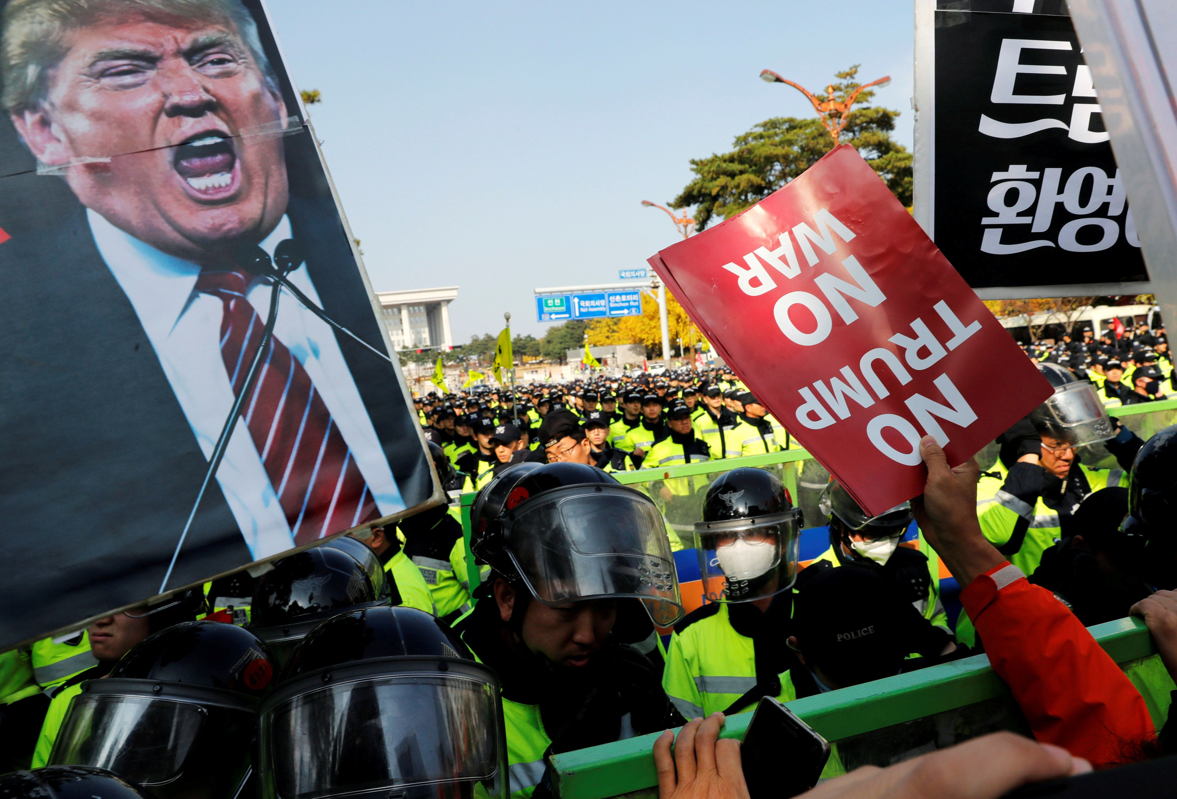 Anti-Trump protesters hold up signs in front of police officers near the South Korean National Assembly where U.S. President Donald Trump made a speech, in Seoul, South Korea, November 8, 2017. REUTERS/Kim Kyung-Hoon     TPX IMAGES OF THE DAY
