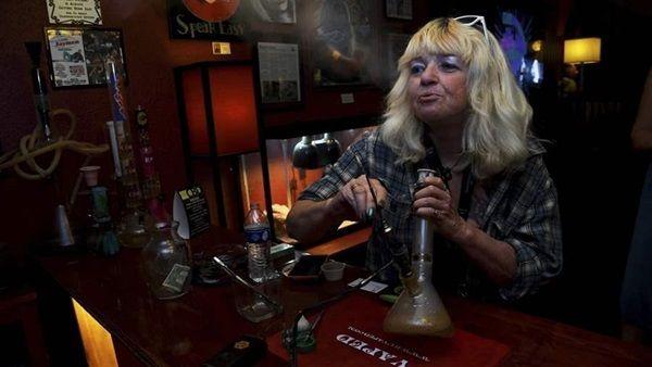 A Colorado woman smokes marijuana at a legal pot lounge in Colorado Springs. Lawmakers have legalized recreational marijuana