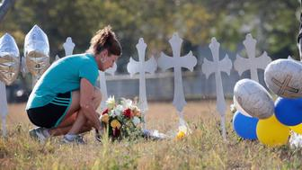 SUTHERLAND SPRINGS, TX - NOVEMBER 07: Cindy Wyatt of Sutherland Springs lays flowers at a memorial where 26 crosses stand in a field on the edge of town to honor the 26 victims killed at the First Baptist Church of Sutherland Springs on November 7, 2017 in Sutherland Springs, Texas. On November 5, a gunman, Devin Patrick Kelley, shot and killed the 26 people and wounded 20 others when he opened fire during a Sunday service. Durand helps to teach bible study at the church and lost several friends in the shooting.  (Photo by Scott Olson/Getty Images)