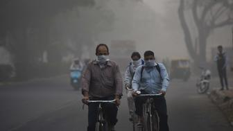 NEW DELHI, INDIA - NOVEMBER 8: Cyclists cover their faces to avoid pollution amid heavy smog, on November 8, 2017 in New Delhi, India. Delhi was enveloped in a thick blanket of haze for the second consecutive day with air quality levels deteriorating. Deputy chief minister Manish Sisodia says all schools to remain shut till Sunday. (Photo by Burhaan Kinu/Hindustan Times via Getty Images)